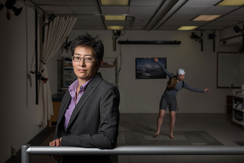 Portrait of Lena Ting with a subject in the background who is covered in motion sensors and balancing on one leg
