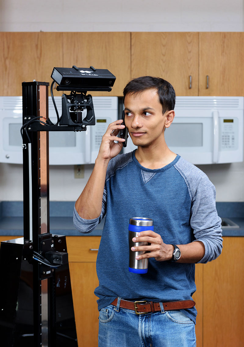 Graduate student in a lab that looks like a kitchen, with a phone to his ear, being interrupted by a robot over his shoulder