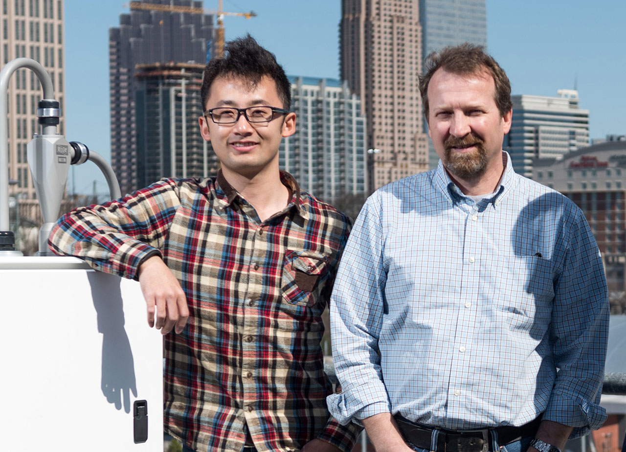 Two researchers standing outside with the city in the background