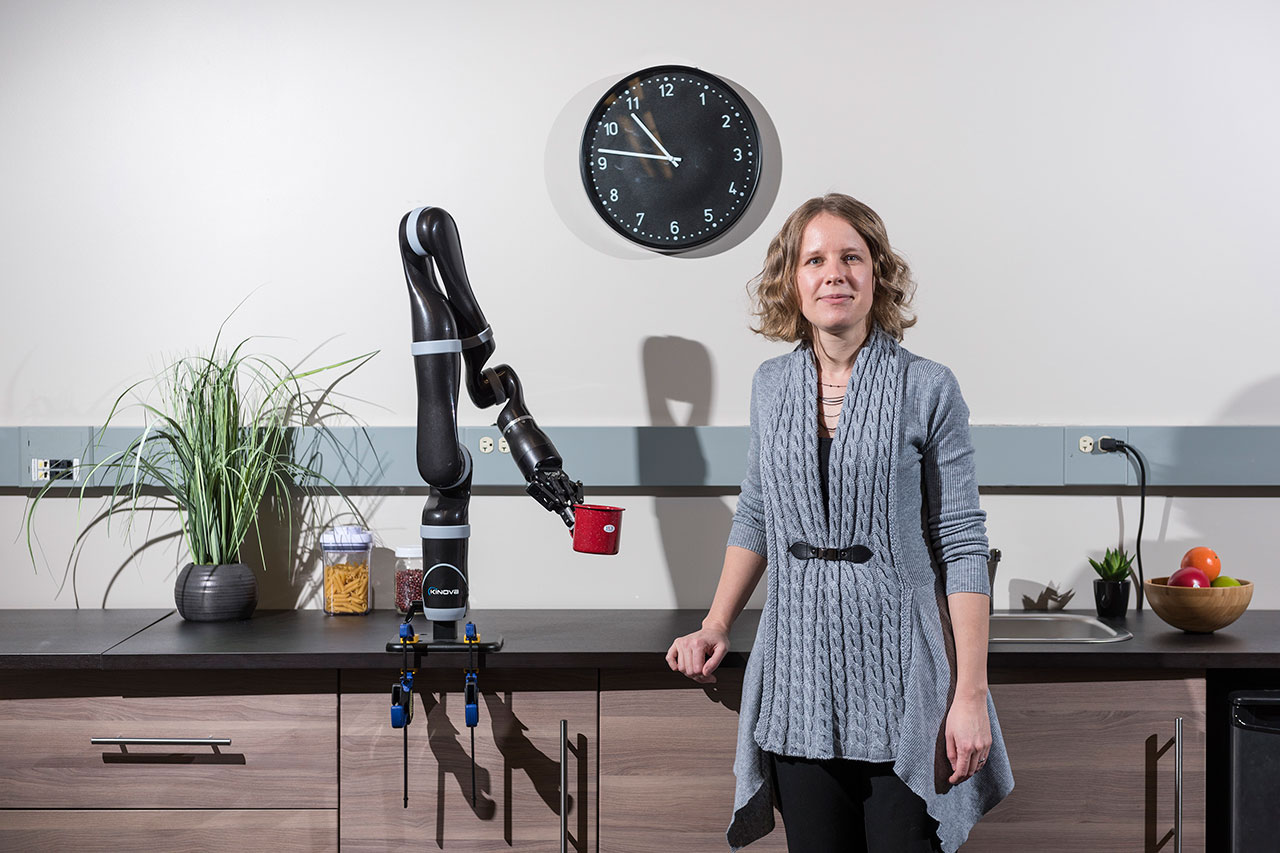 Portrait of Sonia Chernova standing in front of a robotic arm mounted to a counter, which is gripping a coffee cup