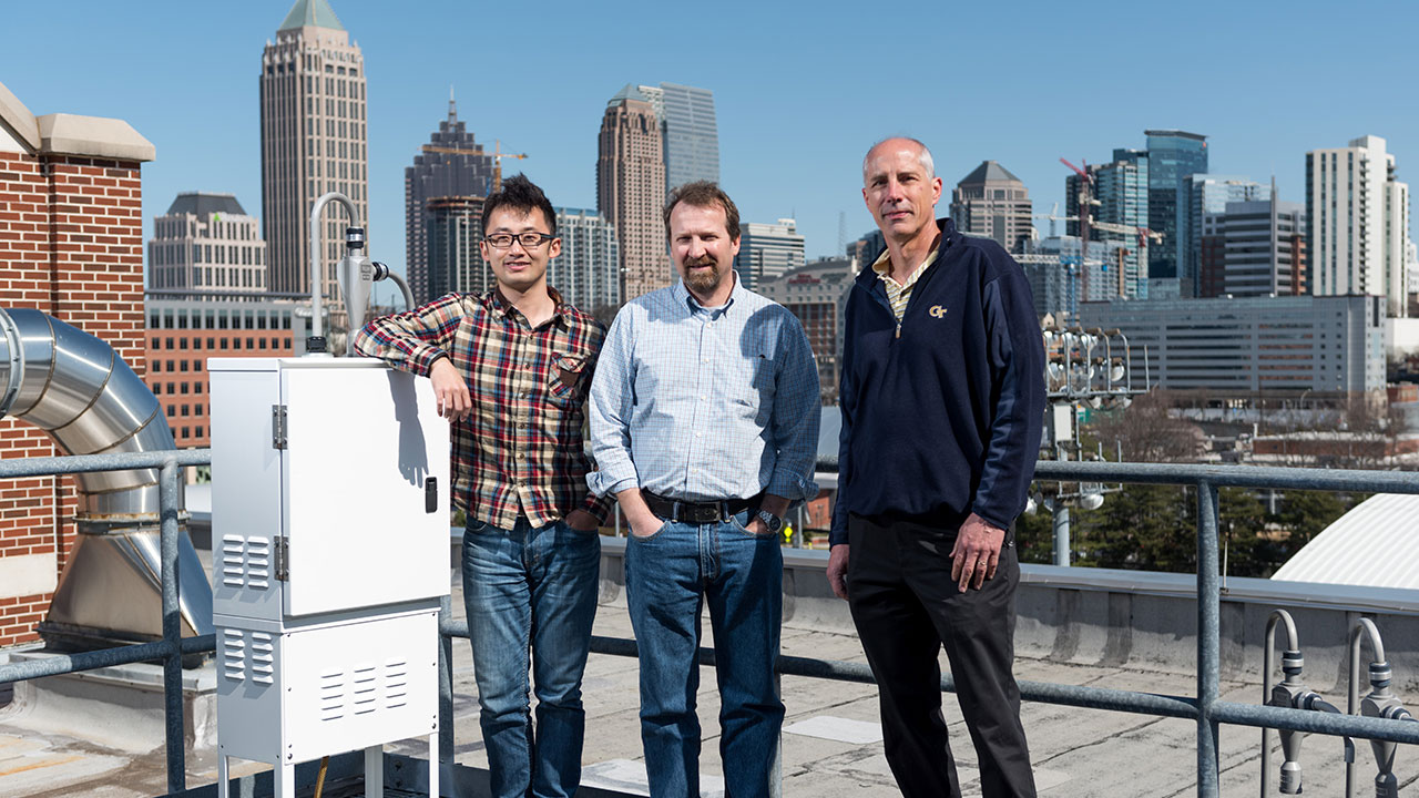 photo - three researchers standing on roof with Atlanta skyline in background