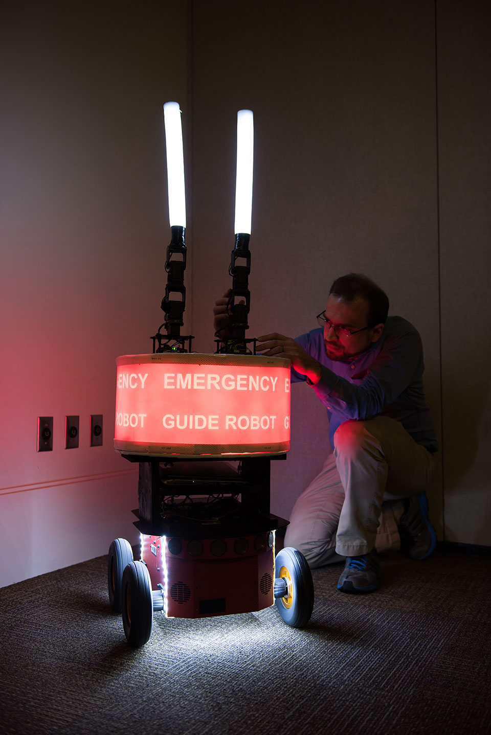 Paul Robinette adjusting the emergency guide robot