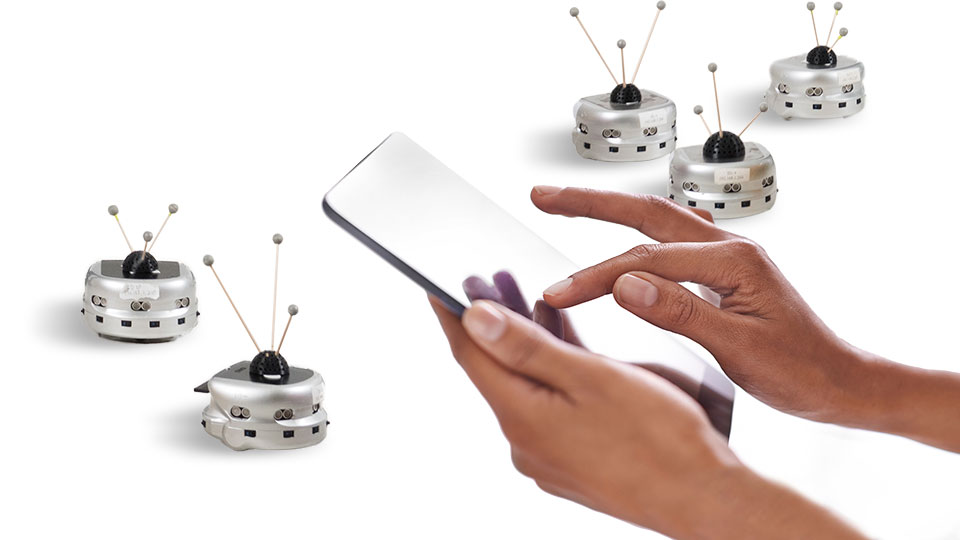 photo illustration - hands holding tablet with small robots in background