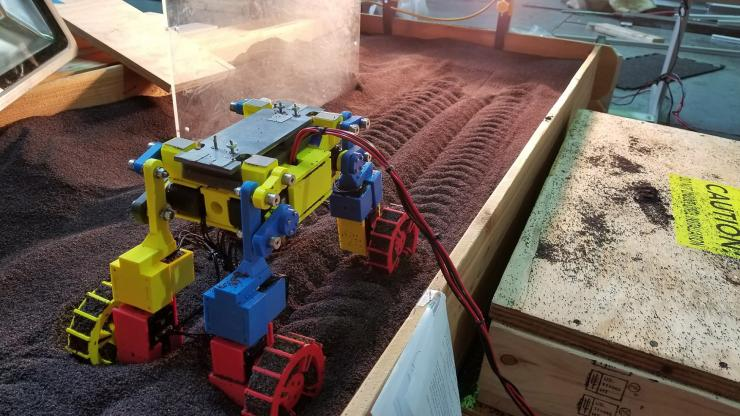 The rover moves over red grains in a wooden container