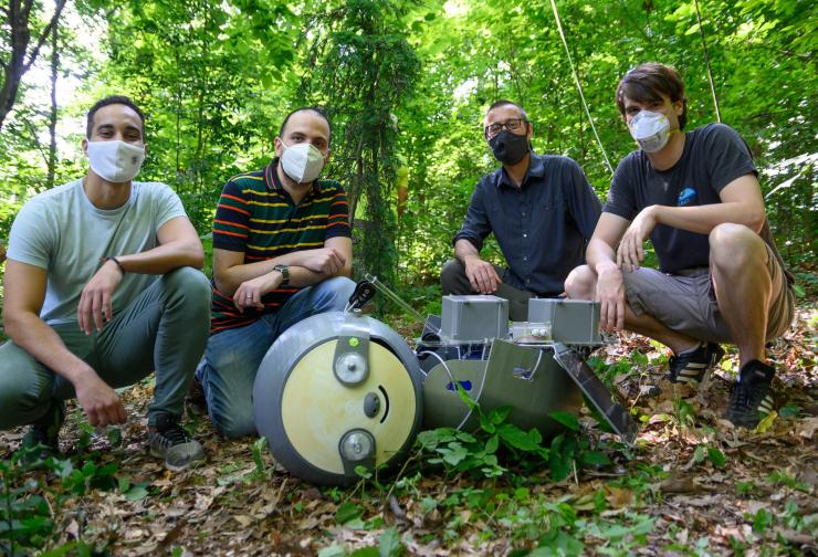 4 researchers kneel near the SlothBot as it lays on the ground. The SlothBot is about half-human height