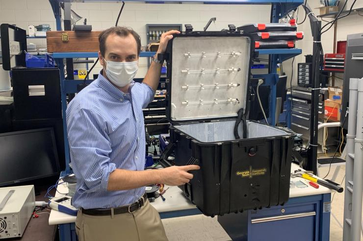 A researcher stands next to the black PPE UV disinfection box holding its lid open.