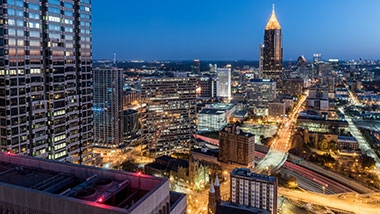The Atlanta skyline at dawn, with streetlights lit and building lights on, while the sun is just barely lightening the sky