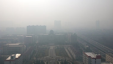 A city scene in China taken from a high building showing a few buildings visible through a severe atmospheric haze with many more buildings barely visible in the background