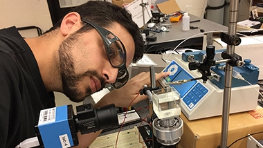 A researcher with eye protection peering closely at some instruments on a lab bench
