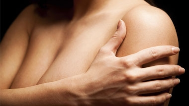 Image of a woman hugging her arms over her chest protectively