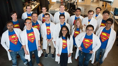 "A group photo of a ""super"" research team wearing superman shirts and lab coats"