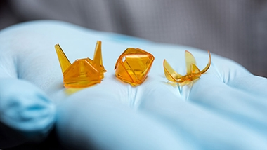 Quarter-size orange plastic origami shapes lie in the palm of a blue-gloved hand