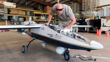 A technician prepares a GTRI TigerShark aircraft for a test flight