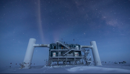 A long-exposure image of the outside of the IceCube observatory with stars above