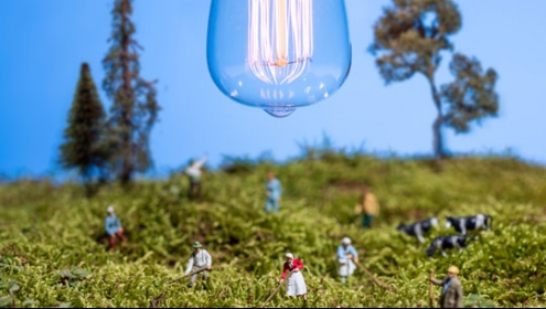 A picture of tiny farmers with a lightbulb overhead.