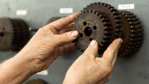 Hands turning a large machine cog