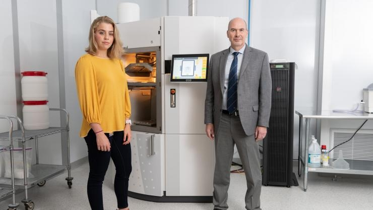 Researchers with 3D printing equipment