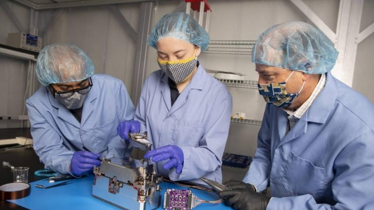 Aerospace Engineering Professor Glenn Lightsey and graduate students Brandon Colón and Lacey Littleton assemble the propulsion system developed at Georgia Tech for the Lunar Flashlight CubeSat. (Credit: Candler Hobbs)