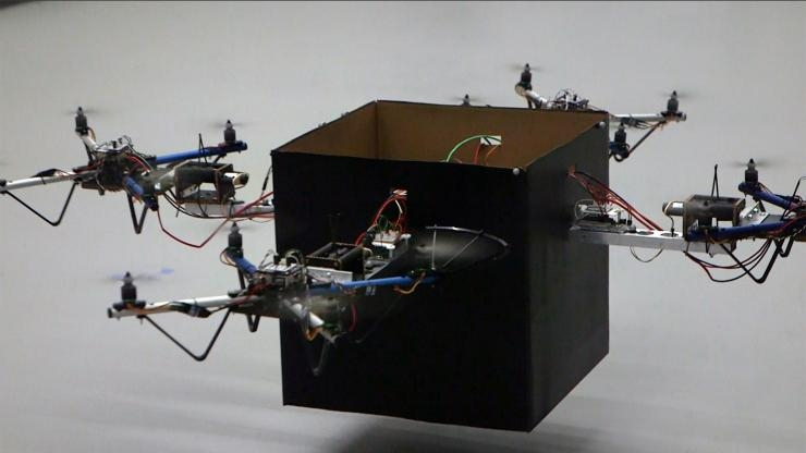 Drones collaborate to lift package