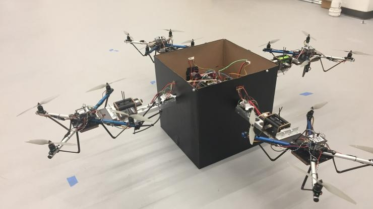 Four drones team up to lift a package