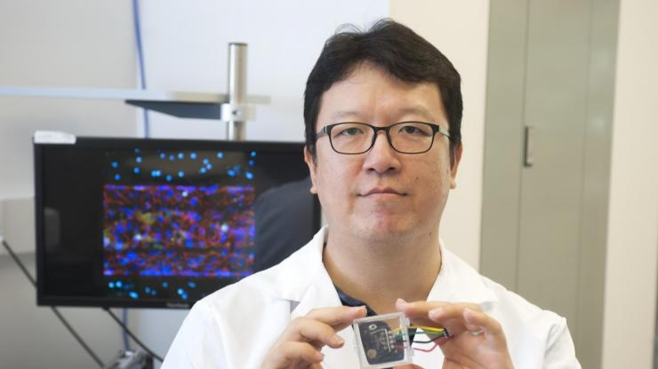 Tony Kim holds up microfluidic chip
