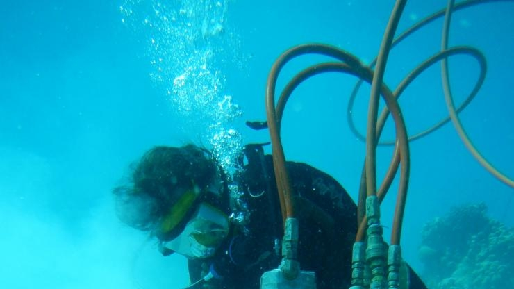 Kim Cobb drills corals underwater in the tropical Pacific